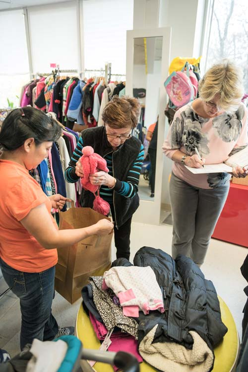 Volunteer shopping assistants work with a client at the Clothes To Kids of Fairfield County Store